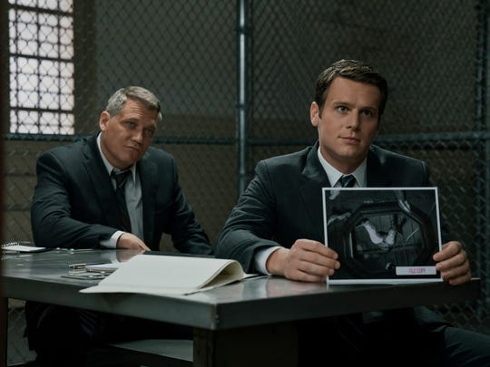 Two men in suits in a prison interrogation room showing a photo to an unseen inmate.