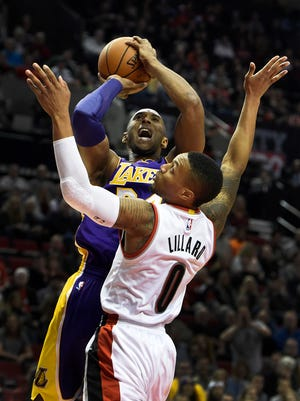 Los Angeles Lakers forward Kobe Bryant (24) shoots the ball over Portland Trail Blazers guard Damian Lillard (0) during the first half of an NBA basketball game on Saturday, Nov. 28, 2015, in Portland, Ore.