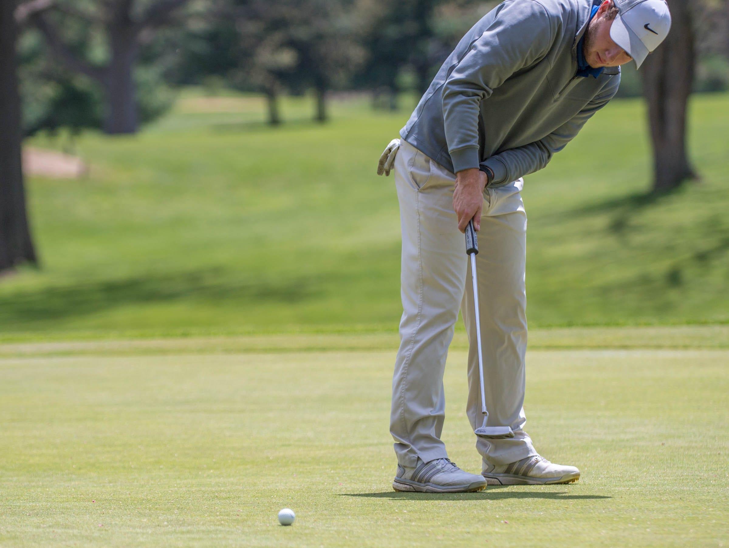 Harper Creek junior Alex Johnson hits his putt during All City High School Golf at Riverside Golf Club on Friday.
