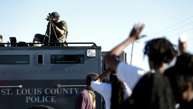 In a scene you would expect to find in a totalitarian country, a member of the St. Louis County Police Department points his weapon at unarmed protesters in Ferguson, Mo., last week. jeff roberson/AP A member of the St. Louis County Police Department points his weapon in the direction of a group of protesters in Ferguson, Mo. on Wednesday, Aug. 13, 2014. On Saturday, Aug. 9, 2014, a white police officer fatally shot Michael Brown, an unarmed black teenager, in the St. Louis suburb. (AP Photo/Jeff Roberson)