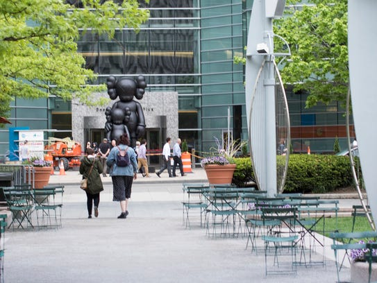 """A 17-foot statue titled """"Waiting"""" by artist Kaws overlooks"""