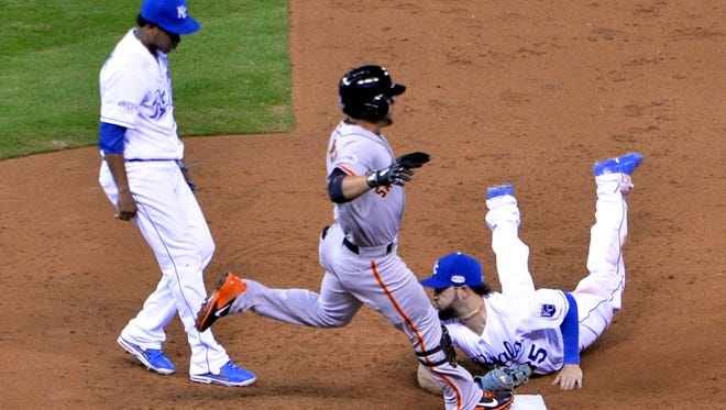 Kansas City Royals' first baseman Eric Hosmer (right) dives to first base to force out San Francisco Giants' center fielder Gregor Blanco (center) in the third inning of the Royals' 7-2 win Wednesday of Game 2 of the World Series. The series is tied at 1-1.