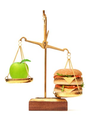 Unhealthy hamburger outweiging a green apple on a weighing scales over a white background