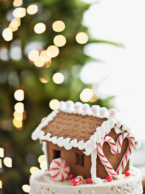 Gingerbread house in front of Christmas tree