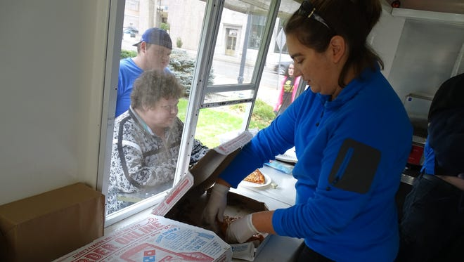 Lisa Burkett, local Domino's franchise owner, serves pizza an at all-you-can-eat charity lunch for United Way. The event raised hundreds of dollars for community improvement initiatives.
