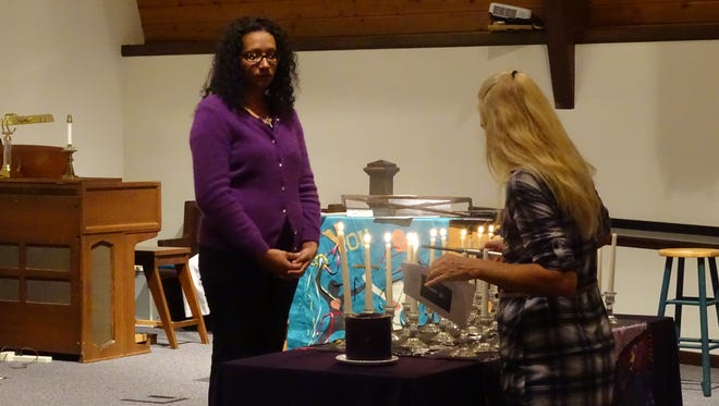 Tisa Beeler lights a candle in honor of her granddaughter whose life, along with other victims of domestic violence, was remembered Thursday night during a vigil at Orchard Hill United Church of Christ.