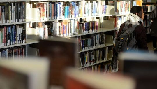 Emmanuel Ubi walks through the stacks at the downtown branch of the Brown County Library in Green Bay