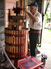 Nick Gattuso tightens a wine press in his Gibbstown