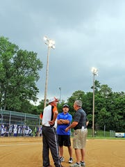 9th Region Tournament organizer Chris Schreiber [right] confers with Ryle and Highlands head coaches Craig Milburn [left] and Rob Coffey about the oncoming rain.