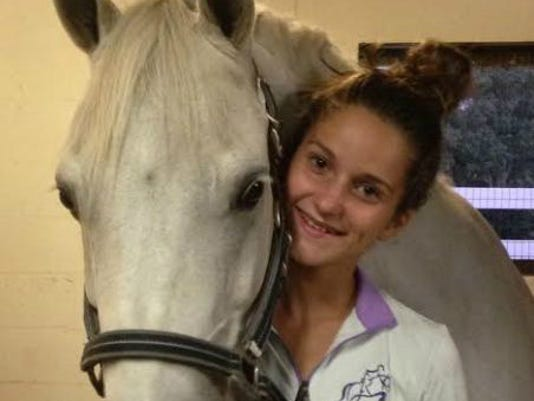 Madison Downs, shown in this submitted photo with her horse, Ian, is seeking to have a zero removed from her school records. Her family has filed a lawsuit, arguing Madison didn't deserve the failing grade because she missed a class at another teacher's request.