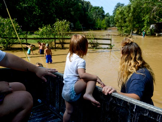 Mckenzie Smith, 2, puts her leg up on the ledge of a truck bed in wanting to join her cousins while they play in the water in the morning hours after flash floods swept through low lands and creek beds at Swink Road in Medon, Tenn., Monday, July 16, 2018.