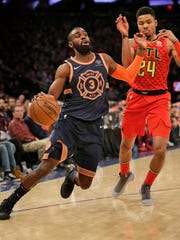 New York Knicks' Tim Hardaway Jr., left, tries to get past Atlanta Hawks' Kent Bazemore during the first half of an NBA basketball game, Sunday, Feb. 4, 2018, in New York.