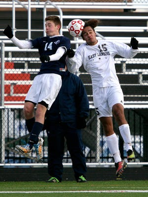 East Lansing's Torey Redmond (15) hits a header against Bloomfield Hills Cranbrook-Kingswood's Kolin Clark.