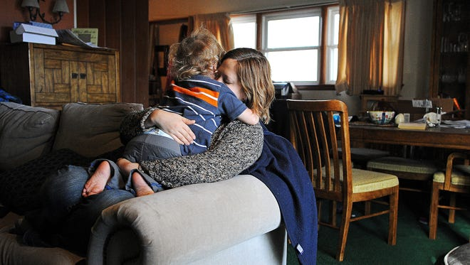 """Kristin Hendrickson embraces her son, Eliyah Hendrickson, 3, after encouraging him to crawl to her Friday, Oct. 30, 2015, at their home in Sioux Falls. Eliyah was diagnosed with Dravet Syndrome when he was five-months-old by a Colorado doctor. """"With Dravet Syndrome then comes a whole grab bag of neurological and some physical issues,"""" George Hendrickson, the boy's dad, said."""