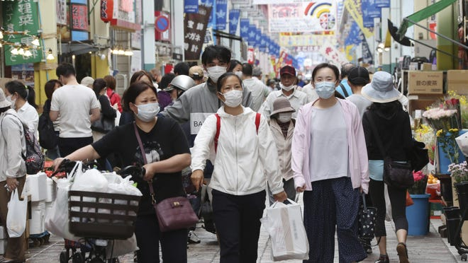 People wearing face masks shop at a mall in Yokohama, near Tokyo, on June 23.