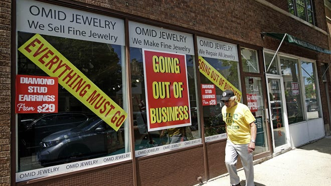 FILE - A man walks past a retail store that is going out of business due to the coronavirus pandemic in Winnetka, Ill., Tuesday, June 23, 2020.  More than 1.4 million laid-off Americans applied for unemployment benefits last week, reported Thursday, July 30, further evidence of the devastation the coronavirus outbreak has unleashed on the U.S. economy.