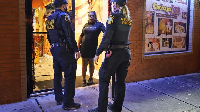 FILE- In this Nov. 12, 2020 file photo, police officers remind a woman in the doorway of a Newark, N.J., restaurant of the new curfew and dining regulations in an area where coronavirus cases have recently spiked. During a Nov. 19, 2020 radio interview, Newark mayor Ras Baraka said that he'll ask residents of New Jersey's largest city to stay home for 10 days starting next week, right before Thanksgiving, in response to a rising number of COVID-19 cases.