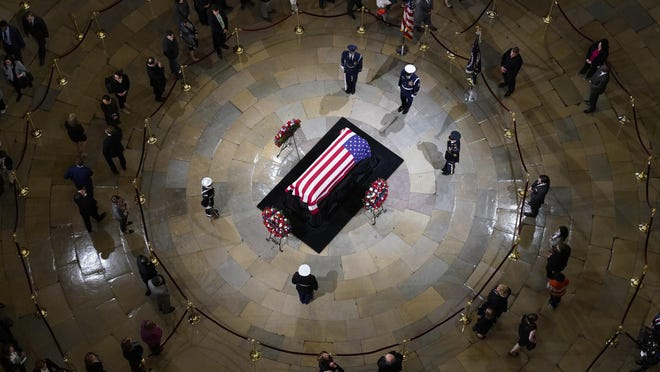 People file past the casket Monday as former President George H.W. Bush lies in state in the U.S. Capitol Rotunda in Washington.