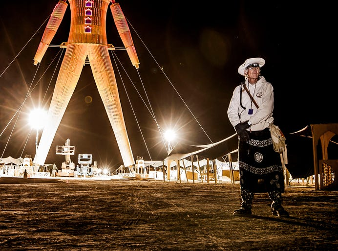 "Doug McGoon of Claremont, California, stands guard in front of ""The Man"" statue while construction crews finish their work at 4:30 a.m. Sunday, Aug. 24, 2014,  hours before the gates open to the Burning Man 2014 arts festival in Black Rock Desert, Nevada.  ""The Man"" is the namesake of the Burning Man Festival. The Man would eventually burn on Aug. 30."