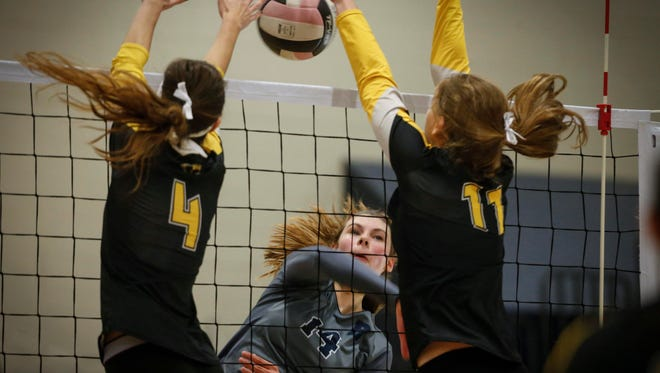 Des Moines Roosevelt sophomore Grace Cumming smashes a hit between Southeast Polk seniors Maya Barker, left, and Emily Plock on Wednesday, Oct. 19, 2016, at Des Moines Roosevelt High School in Des Moines.