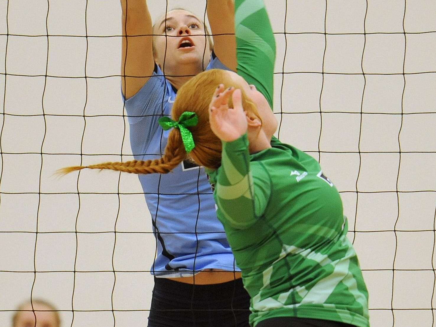 Adena's Carissa Poehler jumps to block the ball hit over the net by Huntington's Kennedy Debord during the game at Adena on Tuesday. The final score was Adena 3, Huntington 0.
