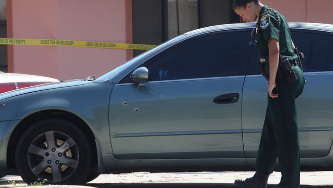 A Lee County Sheriff's Office deputy walks past a Nissan Altima with two bullet holes in the driver's side window while investigating the scene of a shooting at Southward Village in Dunbar on Sunday.