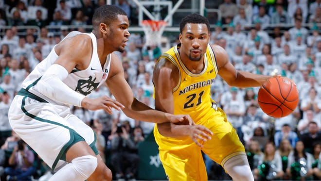Michigan's Zak Irvin drives against Michigan State's Alvin Ellis III during the first half.