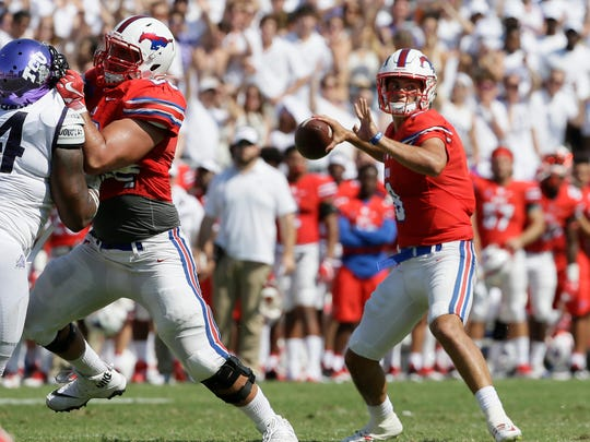 SMU quarterback Ben Hicks (8) looks to pass with a block from teammate offensive lineman Will Hopkins (60) against TCU defensive tackle Joseph Broadnax Jr. (54) during the first half an NCAA college football game in Fort Worth, Texas, Saturday, Sept. 16, 2017. (AP Photo/LM Otero)