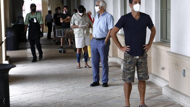 People line up 6 feet apart awaiting an opportunity to shop inside the Publix in Palm Beach on Thursday.