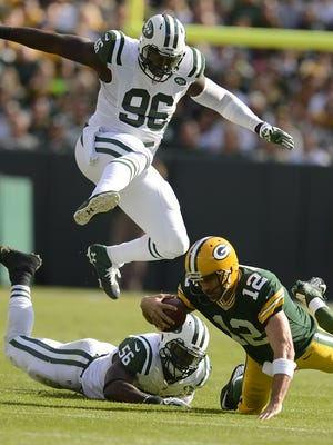 Green Bay Packers quarterback Aaron Rodgers (12) falls down while being chased New York Jets' Muhammed Wilkerson (96) and Demario Davis (56) during their 2014 game at Lambeau Field.