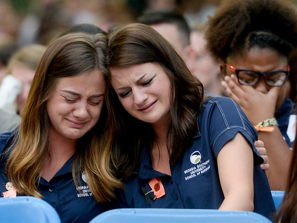 Members of the Georgia Southern Nursing program console each other during a candlelight vigil and memorial service for five nursing students who were killed in a multi-vehicle accident at Georgia Southern's Statesboro campus in Statesboro, Ga. The de