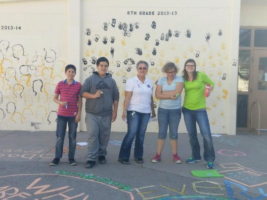 Brian Sainz, Johnathan Gallegos, Penny Antes, Jennifer Curry and Logan Schmaltz, members of HEARTS Youth Coalition, worked to create anti-smoking messages on the concrete walkways of Chaparral Middle School on Thursday afternoon.