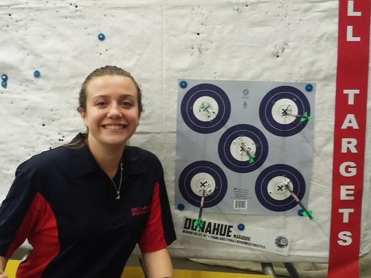 Marjorie Donahue shows off one of her sets of five targets from the NFAA National Indoor Championships, held in March in Louisville, Kentucky.