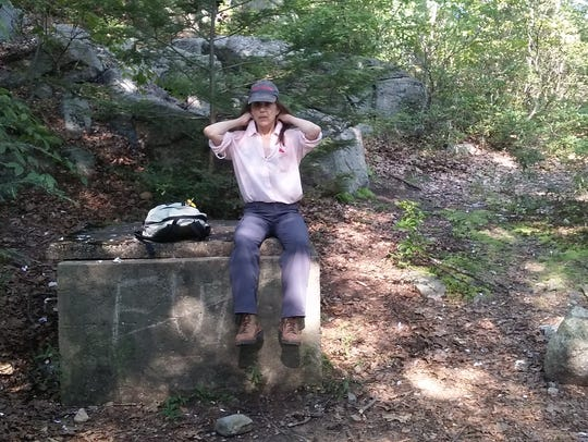 Marilyn Piscitelli sits atop a cistern at Pine Meadow