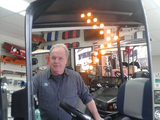 Keith Lokotar's image is reflected in a golf cart mirror