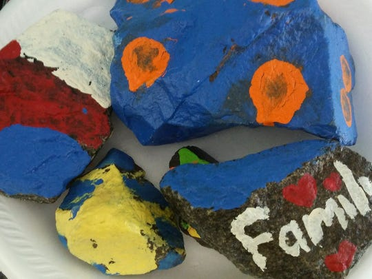"""Playing hide-and-seek with hand-painted rocks has become this summer's """"big thing."""" Community group members decorate and hide rocks around towns — in safe, public spots — for others to find and rehide. Liam Kopp's rock even helped stop a burglary in progress. #ManvilleRocks"""