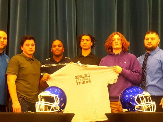 Fort Campbell coach Josh Robins (far right) stands