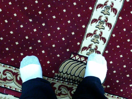 A visitor's feet in socks on the carpet in the sanctuary at the Islamic Organization of Southern Tier.