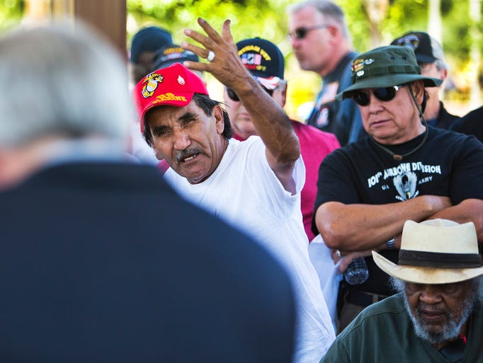 Cruz Salinas, red hat, a U.S. Marine Corps combat veteran who served in Vietnam, angrily questions Rep. David Schweikert , left, at the VA Accountability Rally at Steele Indian School Park. Veterans and their families are angry over recent reports of negligence and ineptitude at Veterans Administration hospitals around the country, especially Phoenix.