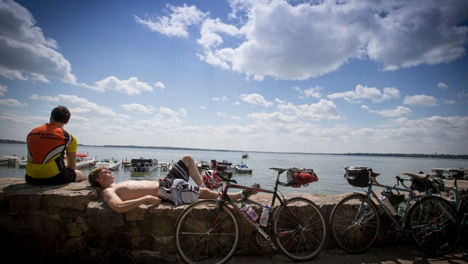 Riders take a break at the water's edge in Clear Lake while on the Register's Annual Bicycle Ride Across Iowa in 2014.