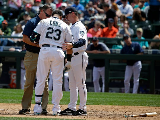 Mariners manager Scott Servais, right, watches as a trainer talks with Nelson Cruz (23). Cruz had to leave the game.