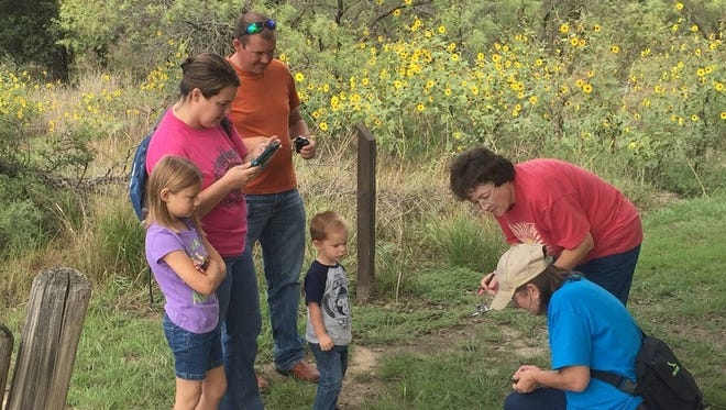 Master Naturalists Terry McKee and Debra Halter (right) teach visitors about Monarch butterfly tagging at Lake Wichita.