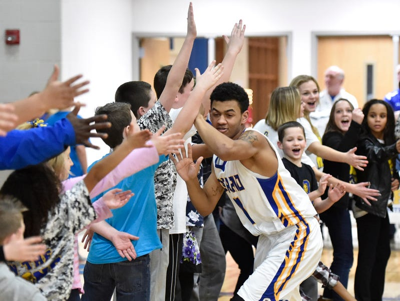 Ontario's Trey Jordan runs the gauntlet of fans during pregame warms last season against Norwalk. The fans will be excited again Friday night when the Warriors play Mansfield Senior for the first time ever.
