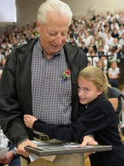John VanDenBerg hugs his granddaughter Kelsey, 10, during the annual Veterans Day Assembly at Our Lady of Sorrows.