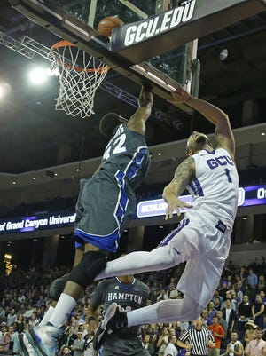 GCU's Grandy Glaze (1) lays the ball off the glass for a basket past the reach of Hampton's Dionte Adams (32) at GCU Arena on Nov. 30, 2015 in Phoenix, Ariz.