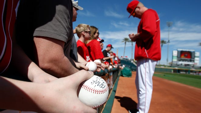 Mat Latos signs autographs for fans before a game against the Cleveland Indians in Goodyear on Feb. 26.