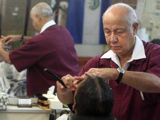 Dimas Montalvo uses a straight razor to shave long-time customer Alan Hairston
