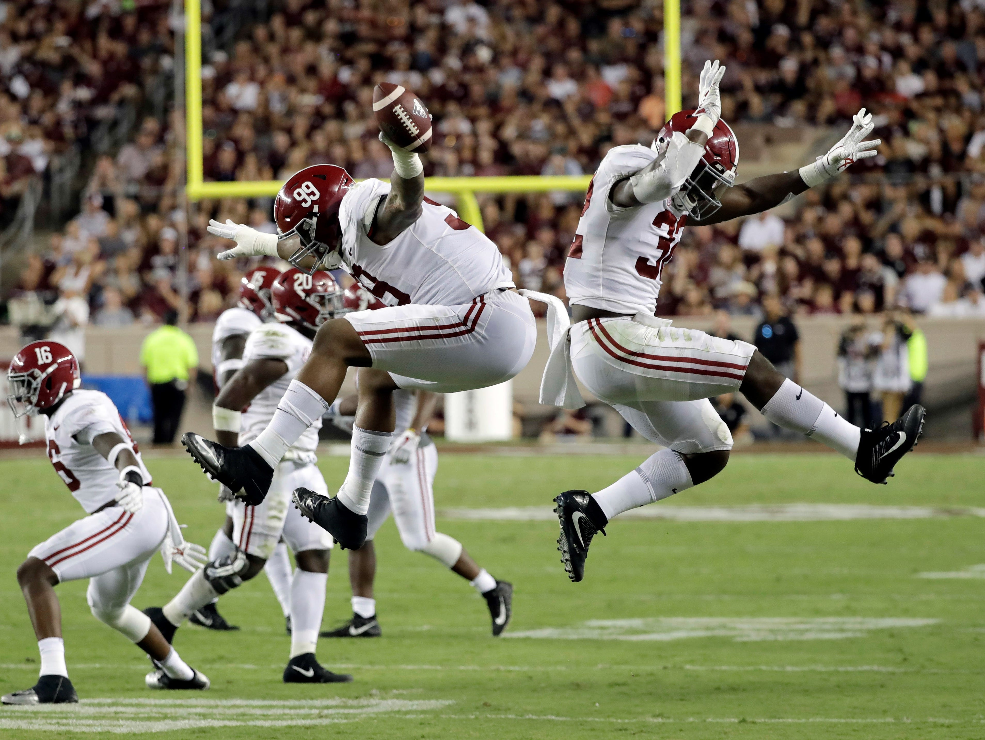 Alabama's Raekwon Davis (99) celebrates with Rashaan Evans (32) after recovering a fumble against Texas A&M during the second quarter of an NCAA college football game Saturday, Oct. 7, 2017, in College Station, Texas. (AP Photo/David J. Phillip)