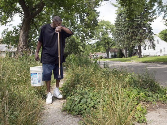 Thomas Reaves stops to rest and wipe sweat from his brow as he carries water in a bucket from the spigot of his Brightmoor neighbor after his water was shutoff in Detroit, Friday, July 18,  2014.  Reaves was left disabled from an accident and has a wheelchair-bound roommate.