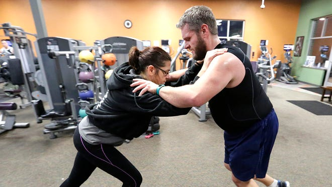 Marie Oosterhouse, a personal trainer at Anytime Fitness in Fond du Lac, works with Chris Hermanns in a push-pull exercise Thursday. Anytime Fitness has seen a burst of memberships since the start of the new year.